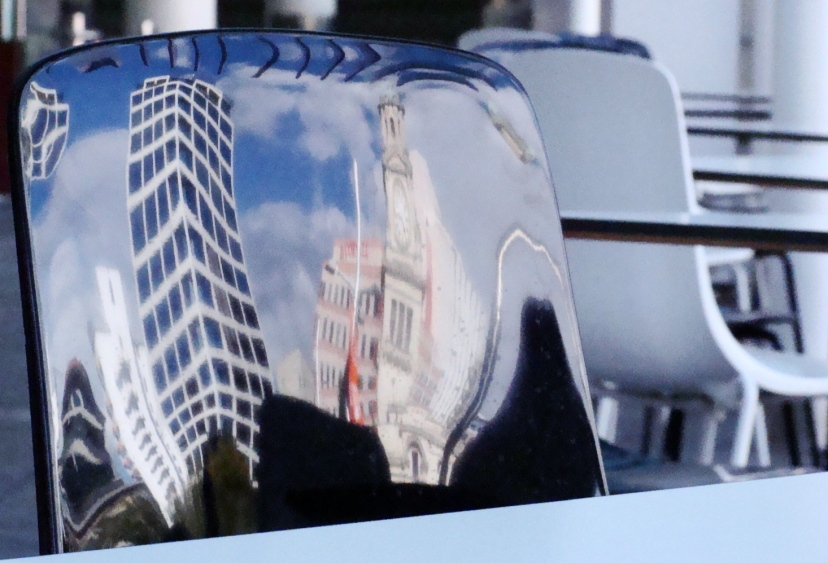 Auckland reflected in chair-back. Bar, Aotea Square, Auckland, NZ