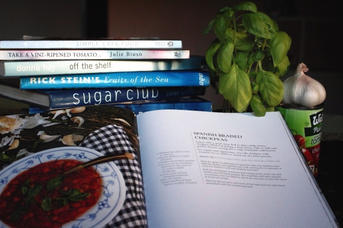Recipe books, garlic, tomatoes and basil. Preparing to make Spanish Braised Chickpeas. Image: Su Leslie, 2016