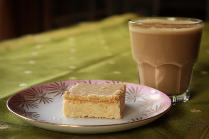 Perfect partnership. Slice of ginger crunch on a patterned china plate with a latte glass. Image: Su Leslie, 2016