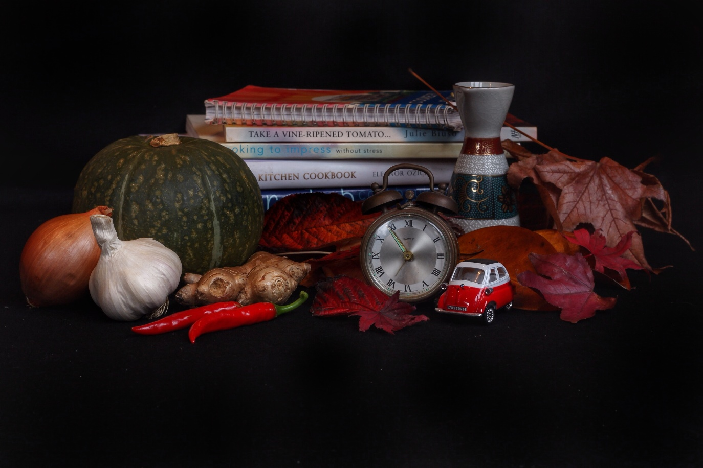Still life with symbolism. Still life of squash, onion, garlic, chilli and ginger with cookbooks, clock, toy car and autumn leaves. Image: Su Leslie, 2017