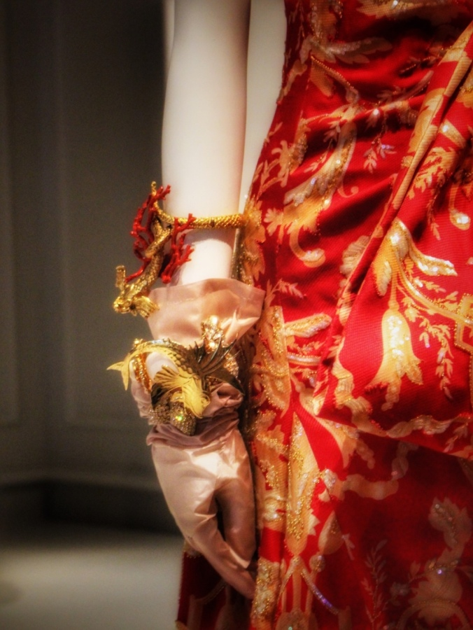 Close up shot of gold women's glove with gold and red dragon design and braclet and red/gold dress -- on mannequin at exhibition 'Dior: 70 Years of Haute Couture', National Gallery of Victoria, Melbourne, Australia. Image: Su Leslie, 2017
