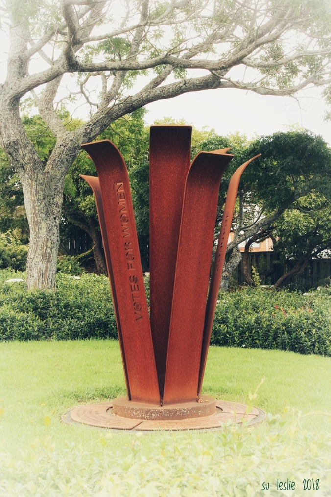 Stylised corten steel camellia forms the Women's Suffrage Memorial (2013), created by MVS Studio and located in Rose Park, Mt Roskill, Auckland. Image: Su Leslie, 2018