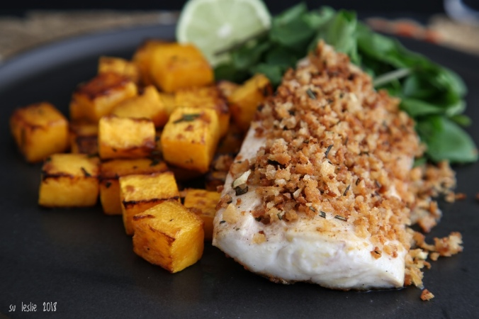 An autumn dish. Close up shot of tarakihi fillet with rosemary lime crumb, roasted butternut squash and watercress salad on black plate. Image: Su Leslie, 2018