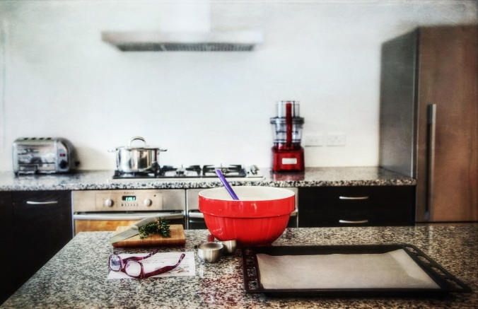 My kitchen; part studio, part laboratory, part drop-in centre. My favourite part of the house and my happy place. Image: Su Leslie, 2018. Aged shot of modern kitchen with chrome appliances and red mixing bowl in foreground.
