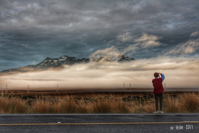 Ruapehu dawn. Road-trip with the boy-child. Shot of young man photographing morning mist shrouding Mt Ruapehu, New Zealand. Su Leslie, 2017