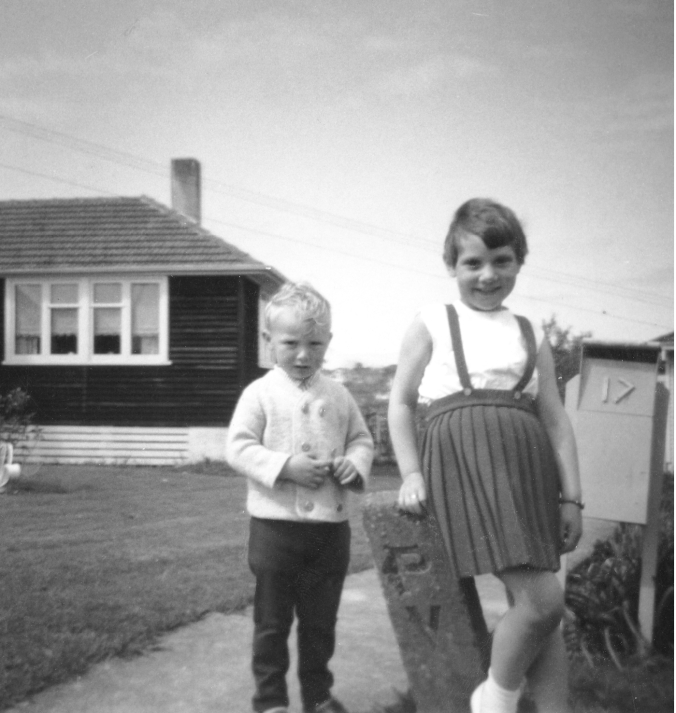 black and white, two children aged 5 and 3 standing by letterbox outside a typical New Zealand house of the 1960s.